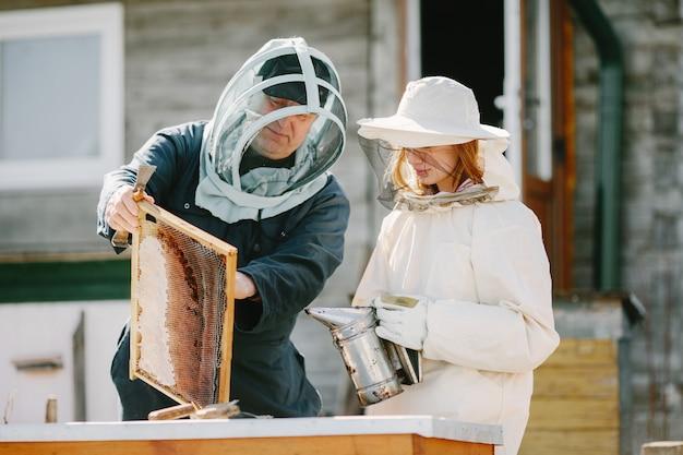 Dwóch pszczelarzy pracujących w pasiece. praca w kombinezonie.