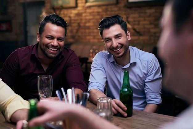 Dwóch radosnych mężczyzn spędzających czas w pubie