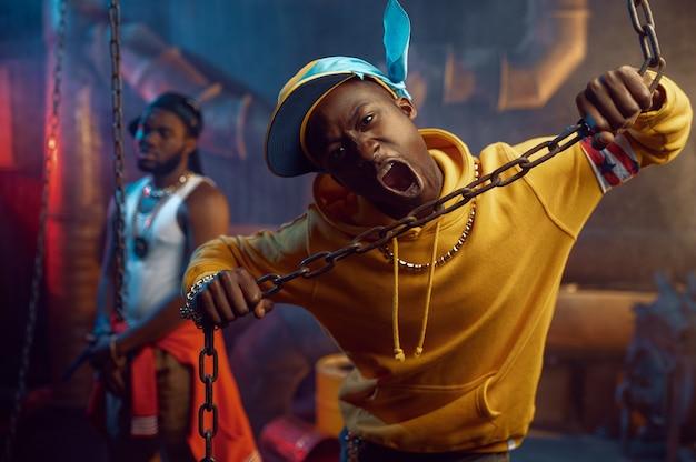 Dwóch raperów, występy break dance z fajną undergroundową dekoracją. wykonawcy hip-hopu, modni rapujący, breakdance