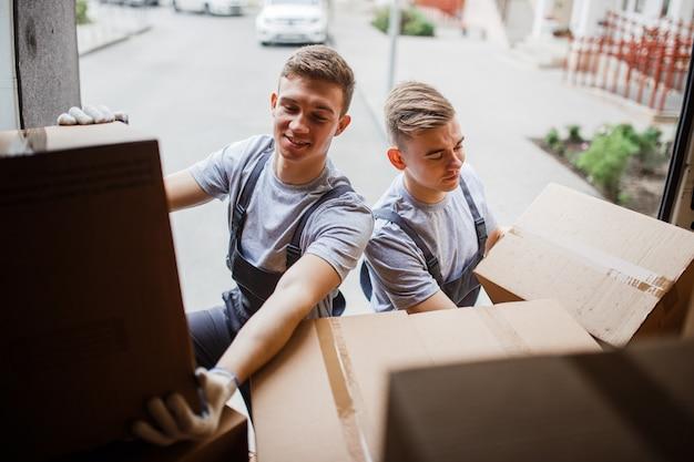 Dwóch robotników w mundurach rozładowuje furgonetkę pełną pudeł