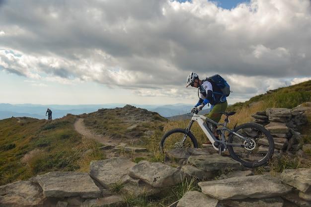 Dwóch rowerzystów jeździ ścieżką na szczycie pasma górskiego na tle pięknego nieba