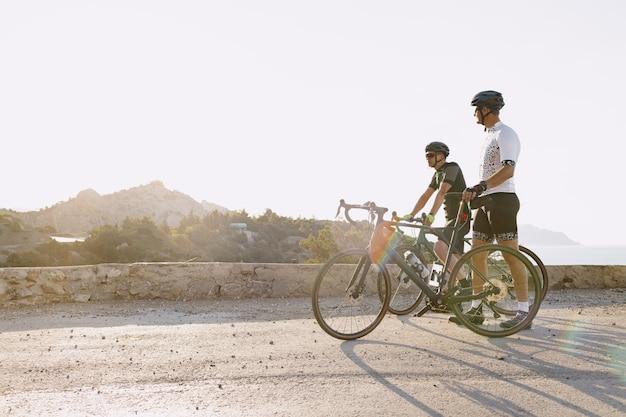 Dwóch rowerzystów płci męskiej stoi na nadmorskiej drodze i odpoczywa