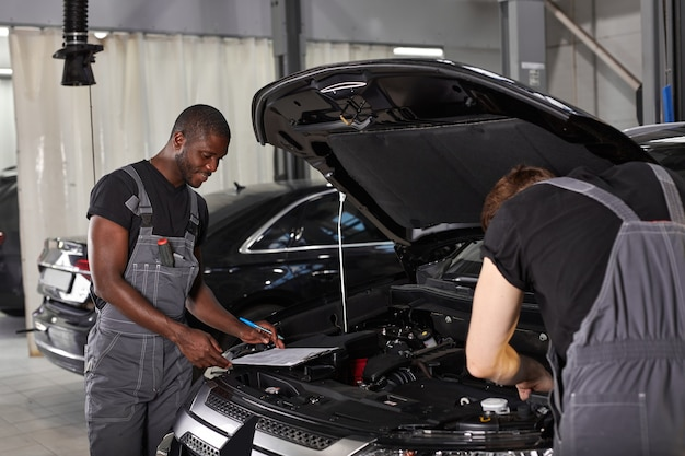 Dwóch różnorodnych mechaników samochodowych współpracujących przy badaniu silnika samochodowego
