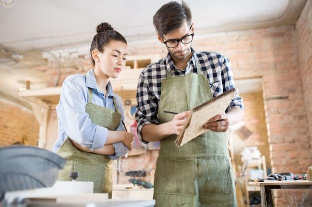 Dwóch rzemieślników pracujących w sklepie stolarskim