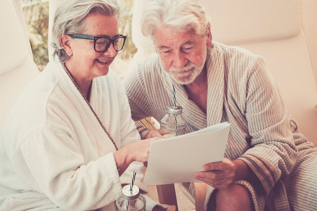 Dwóch seniorów patrzących na menu ośrodka i wybierających coś na ten temat - masaż i wspólne siedzenie