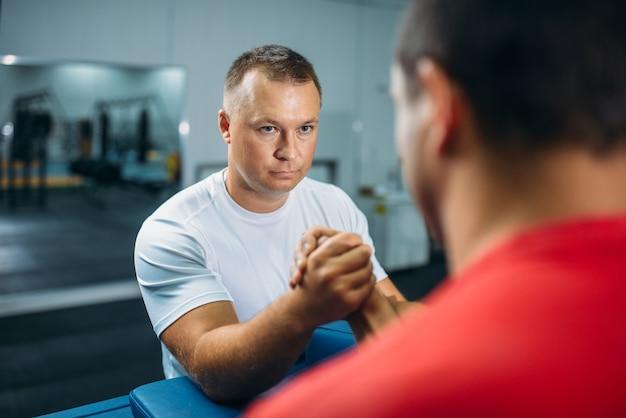 Dwóch siłaczy na rękę przy stole z kołkami, trening