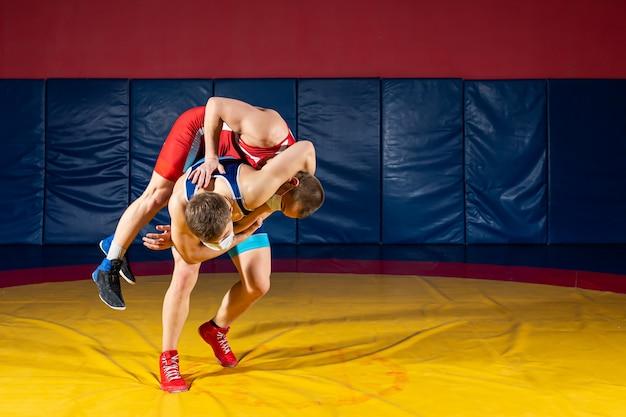 Dwóch silnych zapaśników w niebieskich i czerwonych rajstopach zapaśniczych rzuca biodrem na żółty dywan zapaśniczy na siłowni.