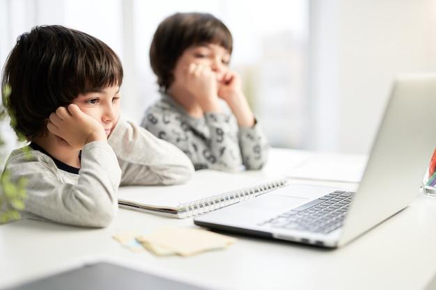 Dwóch skoncentrowanych małych latynoskich chłopców, braci bliźniaków patrzących na ekran laptopa podczas lekcji online dla dzieci, siedzących przy stole w domu. selektywne skupienie