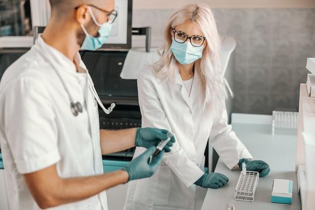 Dwóch skupionych naukowców trzyma probówki z krwią i prowadzi badania nad lekiem na koronawirusa.