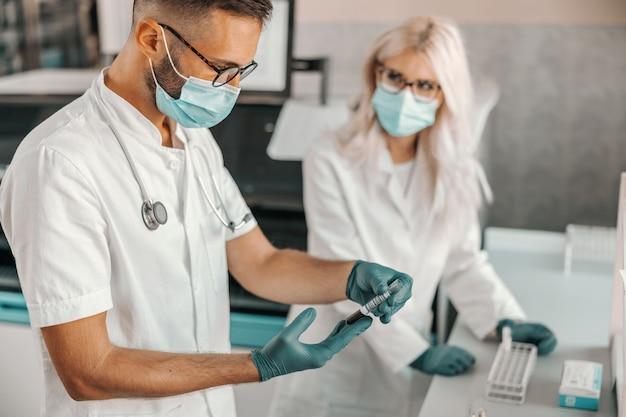Dwóch skupionych naukowców trzymających probówki z krwią i prowadzących badania nad lekiem na wirusa koronowego