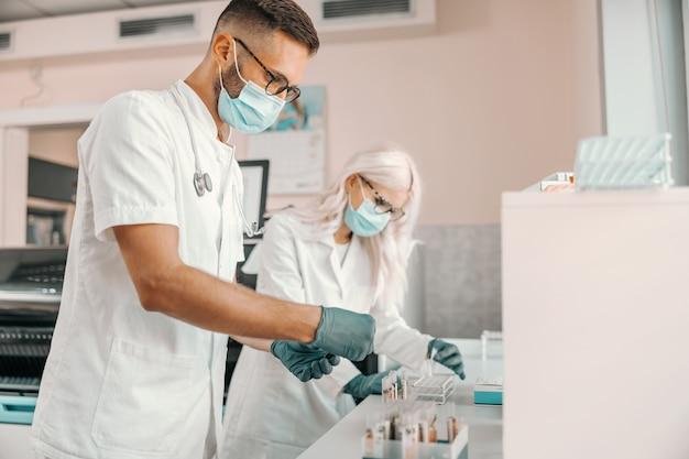 Dwóch skupionych naukowców w gumowych rękawiczkach i maskach na twarz trzymających probówki z krwią i prowadzących badania nad lekiem na koronawirusa.