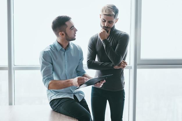 Dwóch skupionych współpracowników płci męskiej pogrążonych w dyskusji, stojąc w nowoczesnym biurze