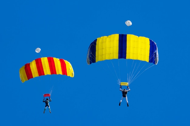 Dwóch spadochroniarzy na tle błękitnego nieba
