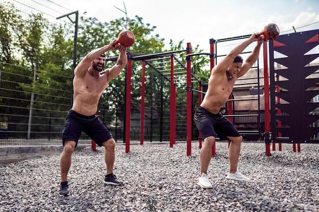 Dwóch sportowców mężczyzn pracujących z kettlebell na ulicy siłowni ulicy.