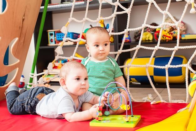 Dwóch sprytnych chłopców bawiących się zabawką w pokoju zabaw