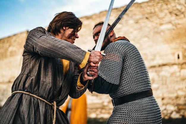 Dwóch starożytnych wojowników w zbroi z bronią walczącą na miecze