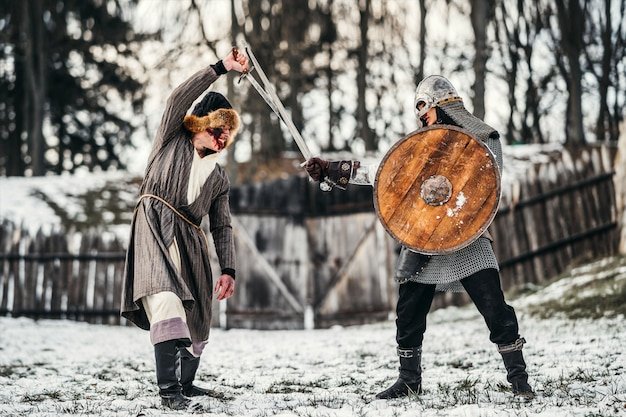Dwóch starożytnych wojowników w zbroi z bronią walczącą z mieczami na śniegu