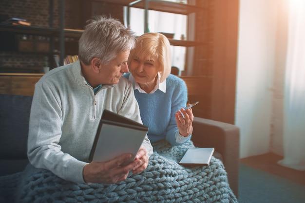 Dwóch starszych ludzi siedzi na kanapie i wybiera dysk cd.