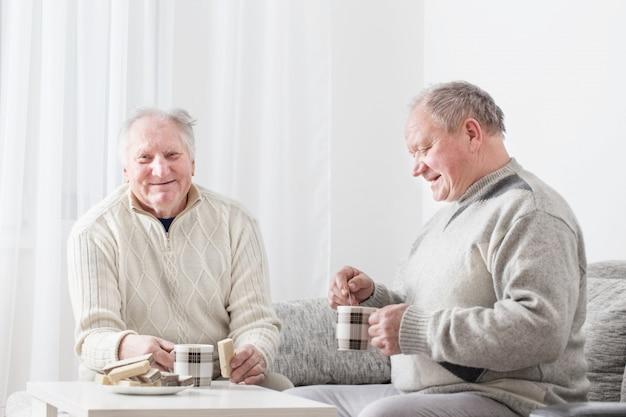 Dwóch starszych mężczyzn z filiżanką herbaty kryty