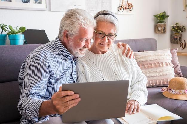 Dwóch starszych osób zostaje w domu, patrząc razem na laptopa. starsza para, koncepcja profilaktyki i pozytywności