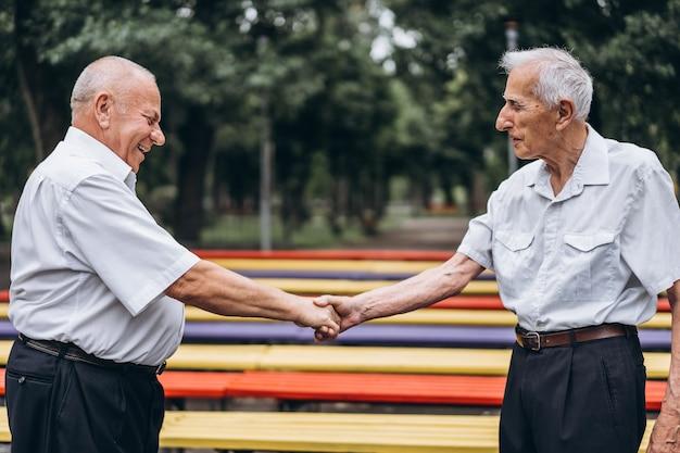 Dwóch starszych starszych mężczyzn rozmawia na świeżym powietrzu w parku miejskim