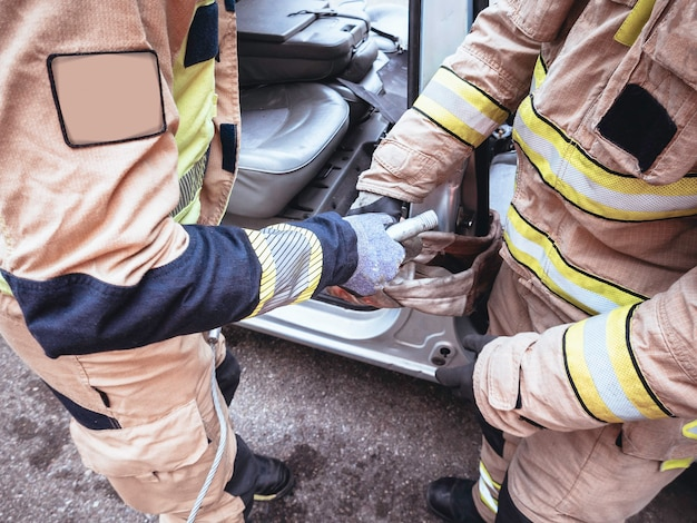Dwóch strażaków trzymających haki z zawiesiami w wypadku drogowym
