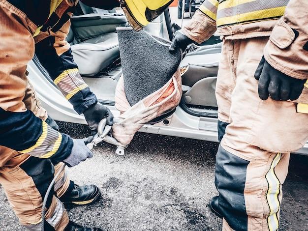 Dwóch strażaków w wypadku drogowym zakłada haki z zawiesiami