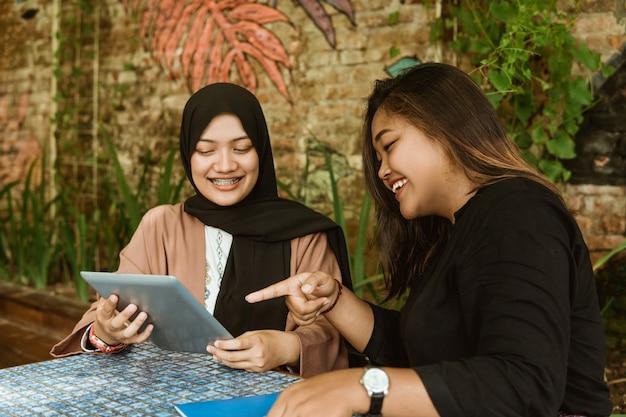 Dwóch studentów dziewczyna za pomocą swojego komputera typu tablet