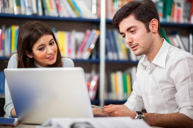 Dwóch studentów korzystających z laptopa w bibliotece