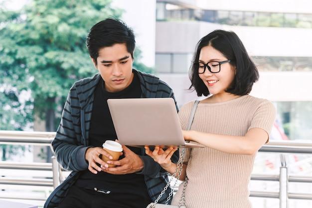 Dwóch studentów nastolatek robi zadanie domowe z laptopem na uniwersytecie