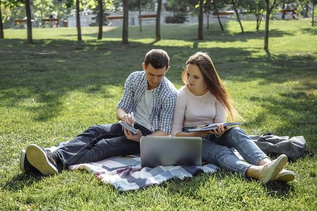 Dwóch studentów przygotowujących się do egzaminu z książką do nauki i laptopem siedzącym na trawniku.