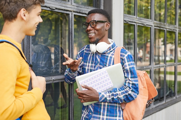 Dwóch studentów rozmawiających na zewnątrz