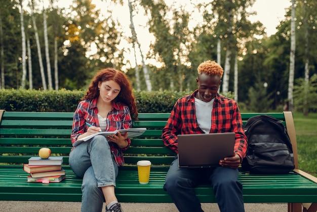 Dwóch studentów siedzi na ławce w parku latem