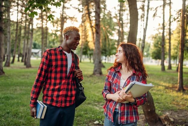 Dwóch studentów spacerujących po trawniku w parku latem
