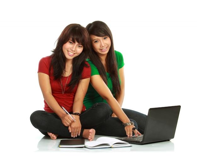 Dwóch studentów stwarzających z laptopa i książek