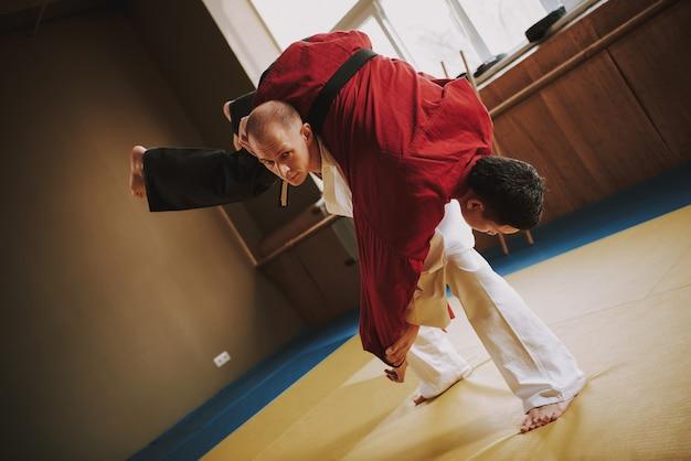 Dwóch studentów sztuk walki w bieli i czerwieni.