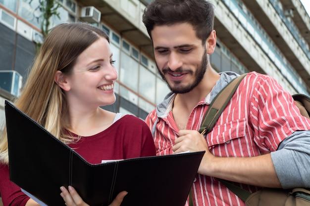 Dwóch studentów uniwersytetu studiujących razem na zewnątrz