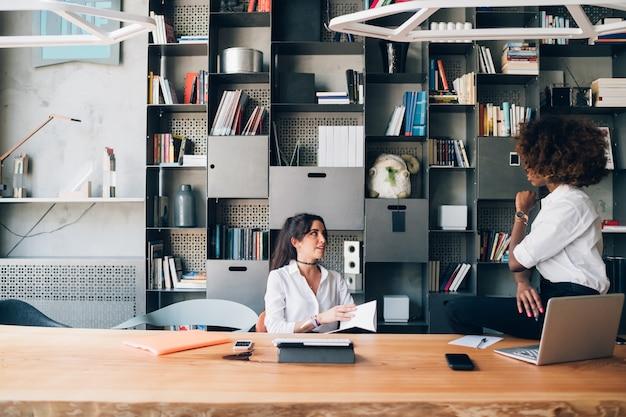 Dwóch studentów wielorasowych omawiających projekt w biurze współpracującym
