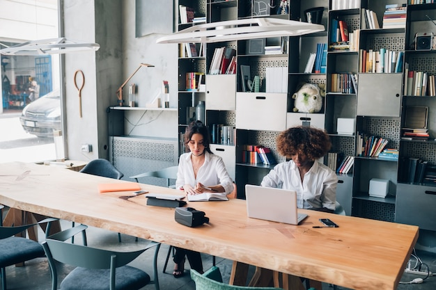 Dwóch studentów wielorasowych pracujących nad projektem w biurze współpracującym