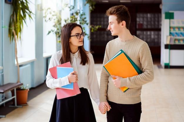 Dwóch studentów wychodzi na korytarz budynku uniwersytetu po zajęciach z materiałami do nauki