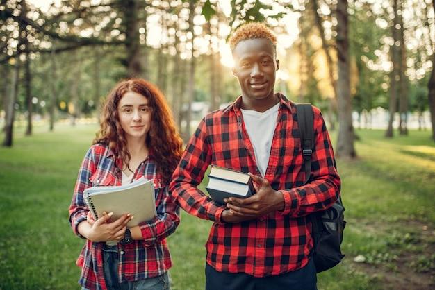 Dwóch studentów z książkami pozuje w letnim parku.