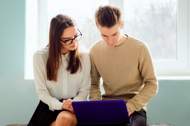 Dwóch studentów z nowoczesnym laptopem podczas przerwy w korytarzu uniwersyteckim. pracowici studenci omawiają niektóre sprawy lub problemy siedząc na ławce w pobliżu okna w kampusie