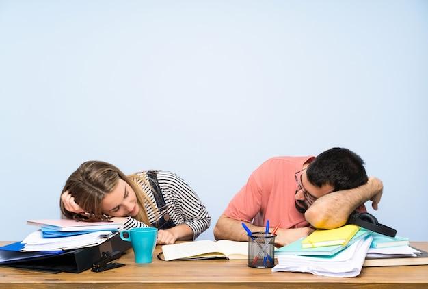 Dwóch studentów z wieloma książkami i spaniem