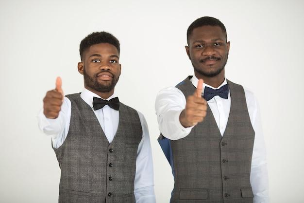 Dwóch stylowych afrykańskich mężczyzn w garniturach na białej ścianie z gestem ręki