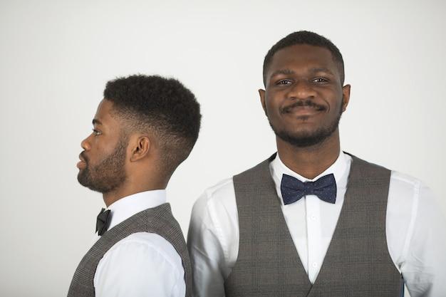 Dwóch stylowych afrykańskich mężczyzn w garniturach na białej ścianie