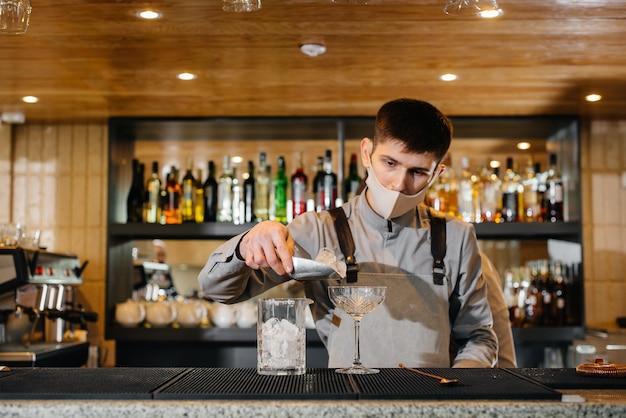 Dwóch stylowych barmanów w maskach i mundurach podczas pandemii przygotowujących koktajle. praca restauracji i kawiarni podczas pandemii.