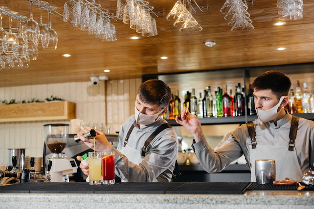 Dwóch stylowych barmanów w maskach i mundurach podczas pandemii przygotowujących koktajle