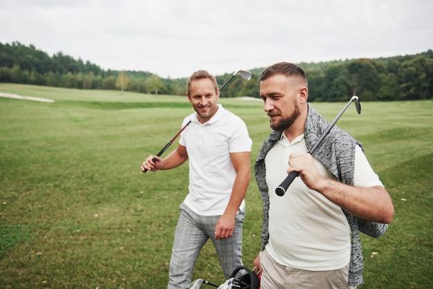 Dwóch stylowych mężczyzn trzymających torby z kijami i spacerujących po polu golfowym
