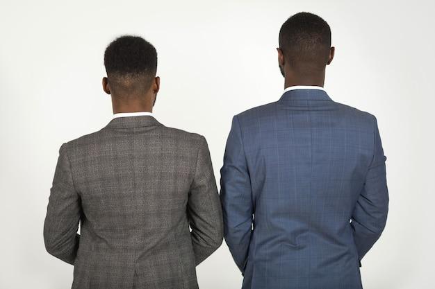 Dwóch stylowych mężczyzn w garniturach na szarym tle wraca