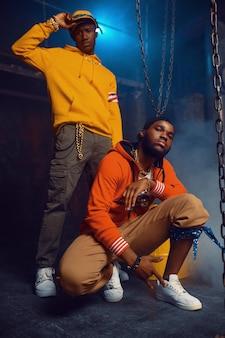 Dwóch stylowych raperów pozuje z fajną podziemną dekoracją. wykonawcy hip-hopu, modni rapujący, breakdance